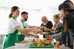 Pauvres personnes recevant la nourriture des volontaires photo stock