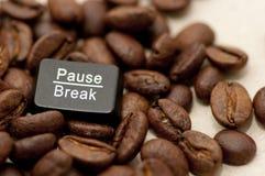 Pauze, onderbrekingssleutel onder koffiebonen stock afbeeldingen