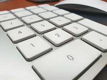 Numeric keypad. White numeric keypad with mouse on second plan royalty free stock photo