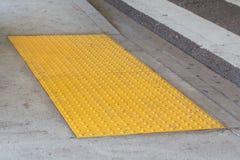 Pavage tactile avec la surface au sol texturisée avec des inscriptions, indicateur Image libre de droits
