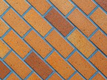 Paved brick background photograph, glazed brown on diagonal slant. Stock Photos