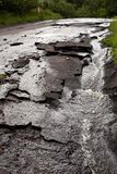 Paved city street destroyed after storm and flood. Rainwater running down a ruined, cracked, city street after heavy rains and flooding Stock Photos