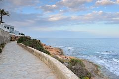 Paved coastal walkway on a summer evening Stock Images