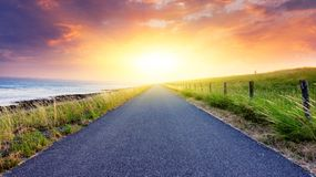 Light from sky . Religion background . Paved country road . Landscape over clouds sunrise . Sunset above road royalty free stock images