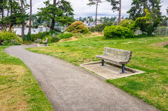 Paved Footpath lined with Wooden Benches Stock Photos