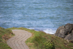 Paved path winds around coastal vista Stock Images