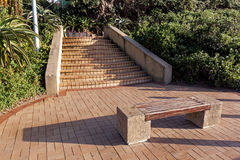 Paved Pathway and Steps with Empty Wooden Bench Royalty Free Stock Image