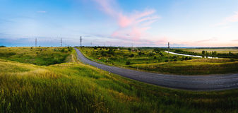 Paved road between the hills in sunset. Royalty Free Stock Photo