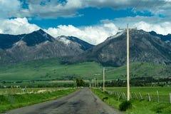 Paved road with leading into the Absaroka Mountain Range near Livingston Montana in Paradise Valley. Paved road with power lines leading into the Absaroka Stock Images