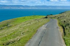 Paved road leads to the blue ocean Stock Image