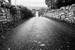 Paved road straight to infinity between the dry stone walls Stock Photo