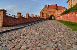 Paved street and the Gothic city gate in Grudziadz Stock Photos
