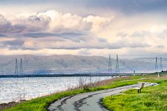 Paved trail following the green grass covered shoreline of south San Francisco bay area, Mountain View, California royalty free stock images