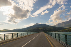 Paved two lane road on bridge crossing lake in scenic landscape and moody sky. Panoramic view from car mounted camera. Summer adve Royalty Free Stock Photos