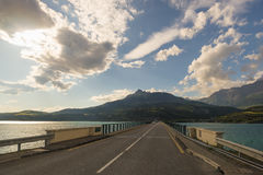 Paved two lane road on bridge crossing lake in scenic landscape and moody sky. Panoramic view from car mounted camera. Summer adve Royalty Free Stock Image