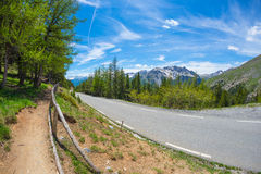 Paved two lane road crossing mountains and forest in scenic alpine landscape and moody sky, fisheye view. Summer adventure and roa Royalty Free Stock Photos