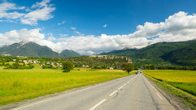 Paved two lane road crossing mountains and forest in scenic alpine landscape and moody sky. Panoramic view from car mounted camera Royalty Free Stock Photo