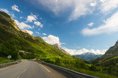 Paved two lane road crossing mountains and forest in scenic alpine landscape and moody sky. Panoramic view from car mounted camera Stock Images