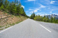 Paved two lane road crossing mountains and forest in scenic alpine landscape and moody sky. Panoramic view from car mounted camera Royalty Free Stock Photos