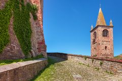 Paved walkway between brick wall and bell tower. Stock Images