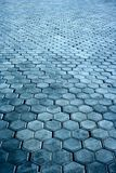 Pavement background. Abstract background / backdrop representing a sidewalk / walkway / footpath flagging surface pattern of blue hexagonal bricks / cobbles / Stock Photo