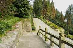 Pavement with balustrade by mountainside road in sunny afternoon Stock Images