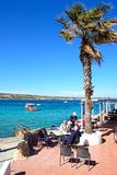Pavement cafe by the sea, Mellieha. Tourists relaxing at a pavement cafe with views across the bay, Mellieha, Malta, Europe Royalty Free Stock Photography