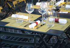 Pavement cafe table, with casual setting. Focus on glasses and cutlery Royalty Free Stock Photo