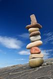 Pavement column. Column of balanced boulders against blue sky stock photography