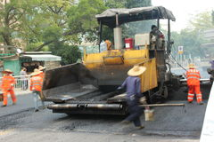 Pavement construction in China ,Asia. The workers are carrying out road construction using large machine equipment in China ,Asia Royalty Free Stock Photography
