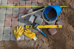 Pavement details, stone blocks rubber hammer level gloves. And tape measure Stock Images