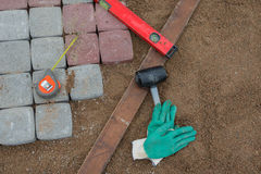 Pavement details, stone blocks rubber hammer level gloves. And tape measure Royalty Free Stock Photography