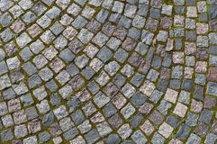 Pavement of granite stone.Old cobblestone road pavement texture,. Grass between stones. Background royalty free stock images