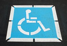 Pavement Handicap Symbol. Blue & white, wheelchair handicap symbol painted on asphalt pavement Stock Photos