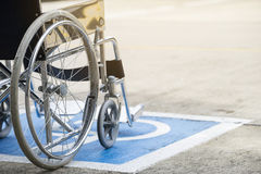 Pavement handicap symbol and wheelchair. Close up Stock Images