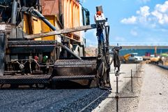 Pavement machine laying fresh asphalt or bitumen Royalty Free Stock Images