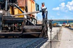 Pavement machine laying fresh asphalt or bitumen Royalty Free Stock Images