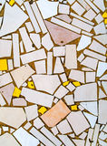 A pavement made out of irregular tiles. A pavement made out of irregular pieces of tiles of various pastel colors - white, very light orange, light red, creamy Royalty Free Stock Images