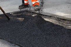 Pavement repair. Asphalt patch being smoothed to repair pavement on a street or roadway stock photo