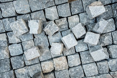 Pavement, stone blocks and construction tools. Construction worker laying cobblestone pavement stones Royalty Free Stock Images