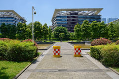 Pavement to modern buildings fenced with hedge in sunny summer Stock Photography