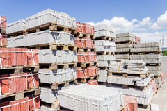 Paver depot. Wooden pallets with different concrete pavers stacked on top of each other on depot on a background of sky royalty free stock photography