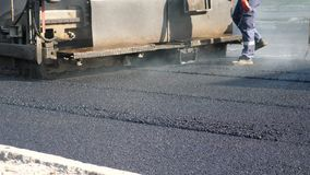 Paver Finisher Placing Layer of Asphalt During Repaving Construction