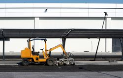Paver laying machine in front of a new build white building.  Royalty Free Stock Images