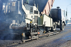 Paver machine laying asphalt, fed by a dump truck Stock Photography