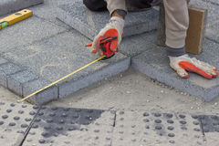 Paver measuring irregular space for laying concrete brick 2 Stock Photos