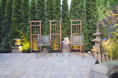 Paver Patio with Garden Decoration. Garden Paver Patio with Trellis Japanese Stone Lantern Pagoda and Bronze Crane Sculpture Royalty Free Stock Photography