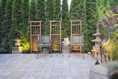 Paver Patio with Garden Decoration. Garden Paver Patio with Trellis Japanese Stone Lantern Pagoda and Bronze Crane Sculpture Royalty Free Stock Photography