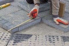 Paver que mede o espaço irregular para colocar o tijolo concreto 2 fotos de stock