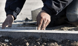 Paver's hand working Stock Image